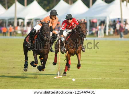 PATTAYA - JANUARY 19: Players fighting for the ball during the final between Thai Polo wearing orange and Axus wearing red shirts at Thai Polo Open on January 19, 2013 in Pattaya, Thailand. - stock photo