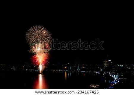PATTAYA - NOVEMBER 28: The colorful firework and skyscrapers at Pattaya bay during Pattaya International Fireworks Festival 2014 on November 28,2014 in Pattaya,Thailand. - stock photo