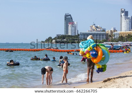 PATTAYA, THAILAND -APRIL 1: Children playing at pattaya beach and toy salesman on APRIL 1, 2014 in Pattaya, Thailand