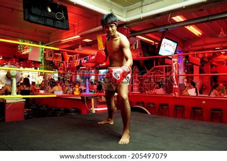 Pattaya, Thailand - circa July 2014 - an unidentified man shows Thai boxing on stage at walking street, Pattaya city, Thailand - stock photo
