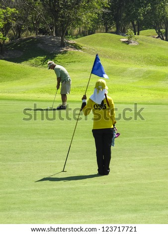 PATTAYA, THAILAND - DECEMBER 28: Unidentified middle aged men playing golf on a scenic golf course near Pattaya, Chonburi on December 28, 2010. Pattaya has 25 golf courses close to the city..