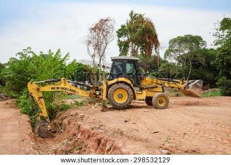 PATTAYA,THAILAND - JULY 20, 2015: The rusty heavy wheel loader excavator machine is working in building site in Pattaya  - stock photo