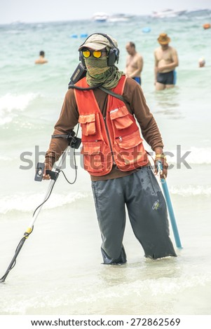 Pattaya, Thailand - March 26 : Man using a metal detector on March 26 2015. Man searching for buried treasure on the beach, lost jewelry and other valuable items. - stock photo