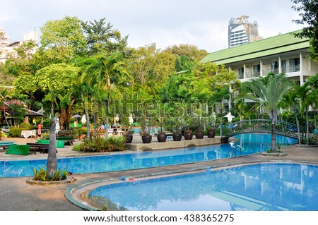 PATTAYA,THAILAND - MARCH 3,2013: the hotel Grounds with tropical gardens and blue swimming pool in North Pattaya.