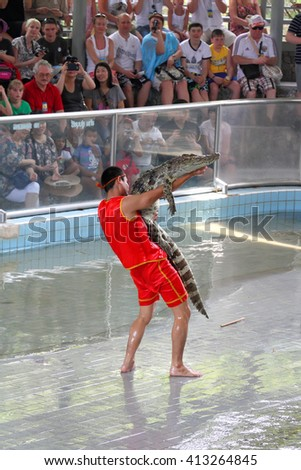 PATTAYA, THAILAND - MARCH 26, 2012: Traditional entertainments for tourists with free photography. Speech of the trainer with crocodiles - stock photo