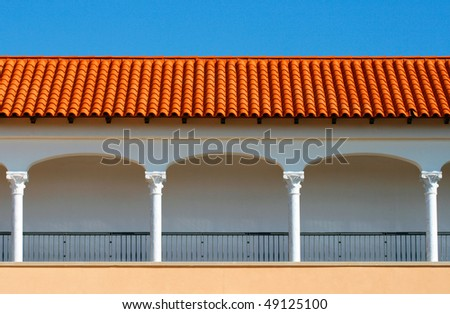 Pattern of a modern covered gallery with the tile roof on blue sky background.It is stylized to classical Spanish style. Caesarea, Israel. - stock photo