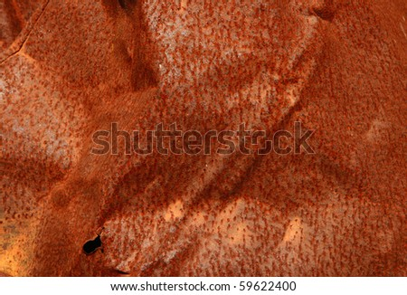 Pattern of a rough surface of rusty metal  with dents, bends,  ribs and holes. - stock photo