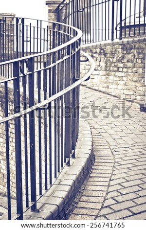 Pattern of curving railings by a stone walkway in retro tones - stock photo
