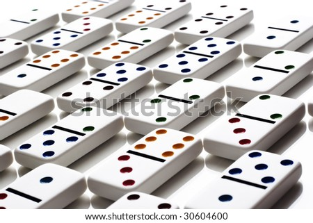 Pattern of dominos on a white, reflective tabletop - stock photo