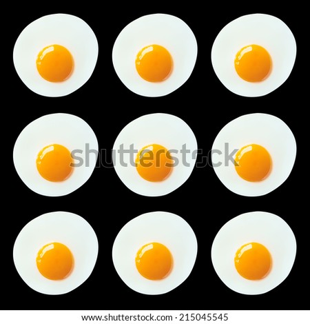 Pattern of fried eggs on black background - stock photo