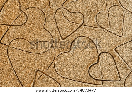 pattern of heart shapes in the sand of a beach - stock photo