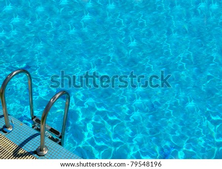 pattern of water of swimming pool with light in it and pool's stairway - stock photo