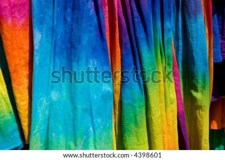 pattern shot of a group of tie-dye t-shirts on a store rack - stock photo