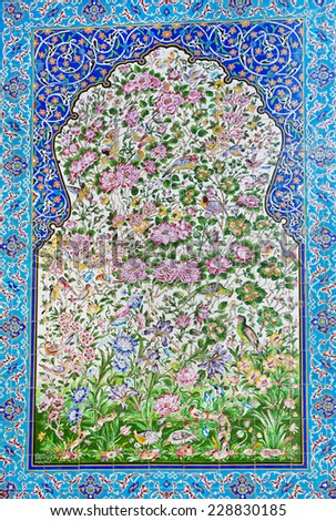 Pattern with forest flowers and birds on the tile on the wall of the old bazaar in Iran - stock photo