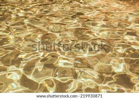 Patterned gold surface water in the pool.