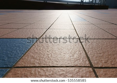 patterned paving tiles, cement brick floor background and sunlight