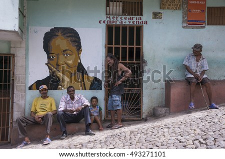 PAUL VALLEY, SANTO ANTAO ISLAND, CAPE VERDE - AUGUST 27, 2015: Men sitting outside a grocery store under the image of a famous Cape Verdean singer