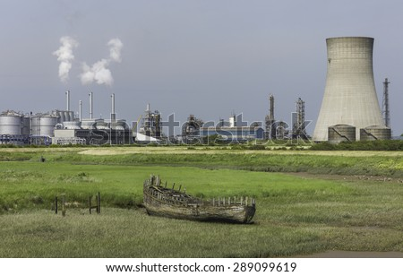 Paull, Holderness, Yorkshire, UK. The large chemical plant with a rotting wooden boat beached on the mud bank of Hedon Haven at low tide near the village of Paul, East Riding of Yorkshire, UK. - stock photo