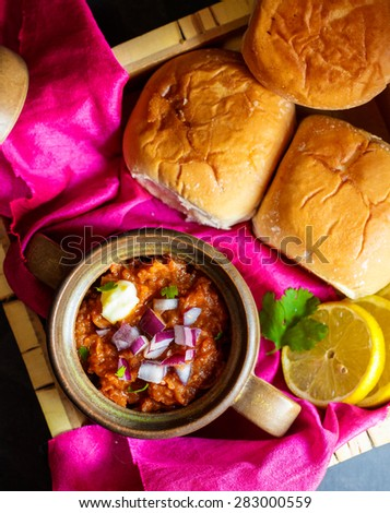 Pav Bhaji Pav Bhaji masala served along with slider buns , lemon wedges,chopped onions and blob of butter on a rich Indian fabric - stock photo