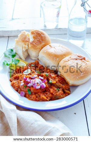 Pav Bhaji Pav Bhaji masala served along with slider buns , lemon wedges,chopped onions and blob of butter on a white plate - stock photo