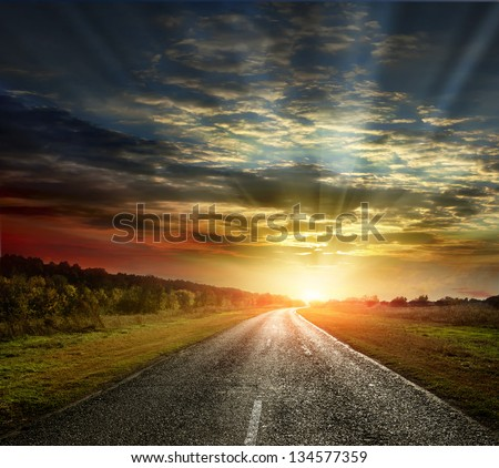 paved country road with surprisingly beautiful sky - stock photo