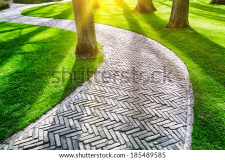 Paved footpath in spring park - stock photo