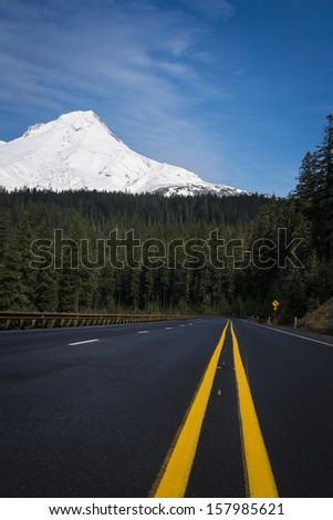 Paved highway with double yellow line beneath snowy Mount Hood, Oregon - stock photo