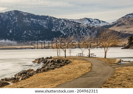 Paved path leading to picnic tables and the river...all unused on this winter day - stock photo