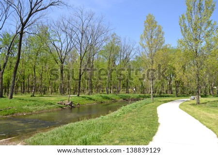 Paved Pedestrian Trail Follows Along a Winding Stream Through Woods in a Park  - stock photo