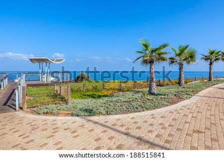 Paved promenade with palms and viewpoint along Mediterranean sea shoreline in Ashkelon, Israel. - stock photo