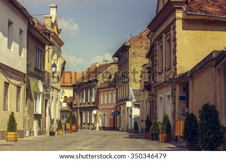 Paved public promenade alley and old medieval houses in the historic center of Brasov city. Brasov is the most visited city in Transylvania, Romania. - stock photo