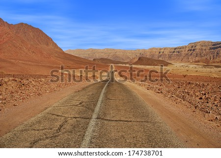 Paved road runs through Arava desert among red mountains in Timna national park, Israel. - stock photo