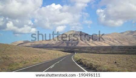 Paved road towards a volcano on Lanzarote island, Spain - stock photo