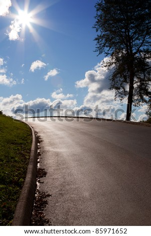 Paved road with sun - stock photo