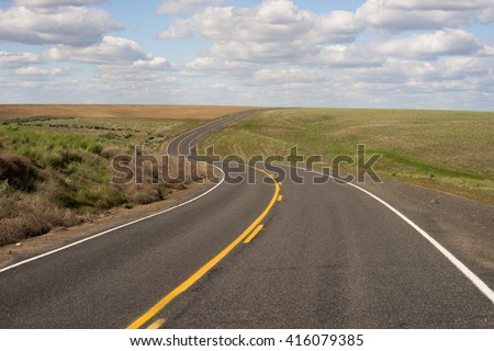 Paved Two Lane Road Highway Transportation White Clouds Blue Skky - stock photo
