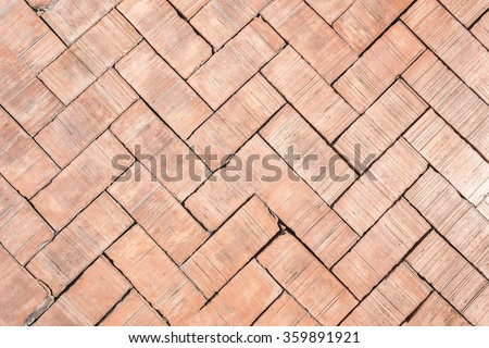Paved with rectangle red brick sidewalk closeup herringbone pattern texture background
