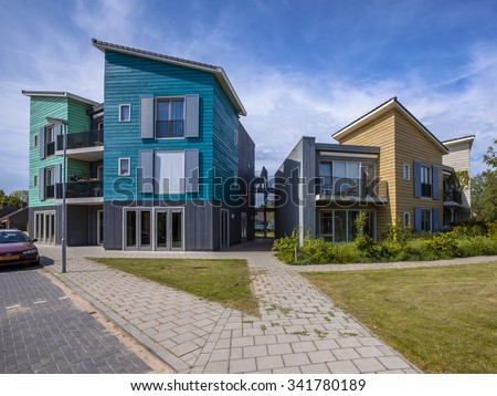 Pavement and park in a Street with modern wooden houses. Contemporary architecture is quite common in the Netherlands - stock photo