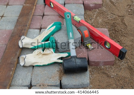 Pavement details, stone blocks rubber hammer level gloves and tape measure  - stock photo