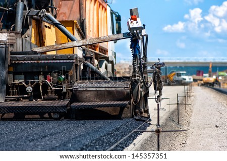 pavement machine laying fresh asphalt or bitumen on top of the gravel base during highway construction - stock photo