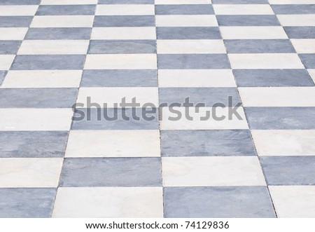 Pavement of grey and white stone plates, looks like a chess bord.