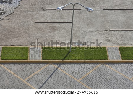 Pavement parking lot construction with green grass and street lamp. View from above. - stock photo