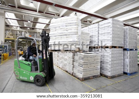 PAVIA, ITALY - 16 APRIL 2012: An employee using a forklift truck to maneuver a pallet load of bagged rice inside the warehouse at a rice processing and packaging plant in Pavia, Italy. - stock photo