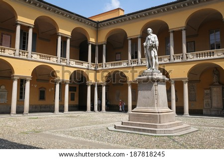 PAVIA, ITALY - JULY 9, 2013: Courtyard of University of Pavia, one of the oldest high education institutes in Europe, with a monument of Alessandro Volta and a group of people in the passageway.  - stock photo
