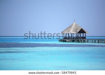 pavilion into the turquoise sea at maldives - stock photo