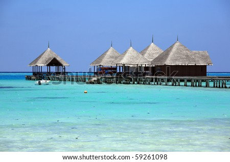 pavilions into the turquoise sea at maldives - stock photo