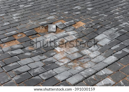 Paving decorative tiles. Poor road. In the middle of the sidewalk collapsed pavement and formed a pit. Dangerous pedestrian traffic. Selective focus is not deep - stock photo