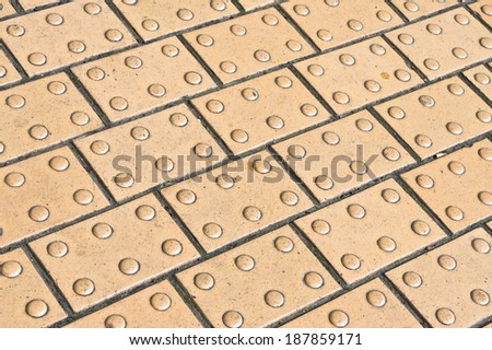 Paving with tactile bumps for aiding blind people - stock photo