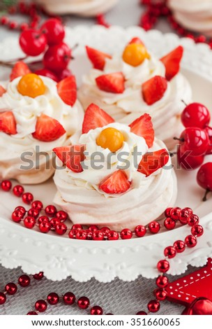 Pavlova meringue cake decorated with fresh strawberry and cape gooseberry on festive background - stock photo