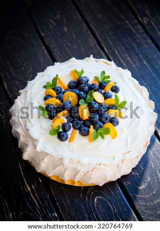 Pavlova meringue sweet dessert cake decorated with whipped cream, blueberries, kumquat citrus  and mint leaves on wooden background - stock photo