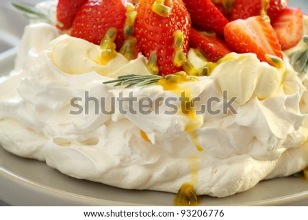 Pavlova with fresh strawberries and passionfruit ready to serve. - stock photo